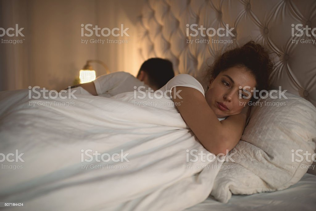 Sad woman having problems in bed with her boyfriend. stock photo