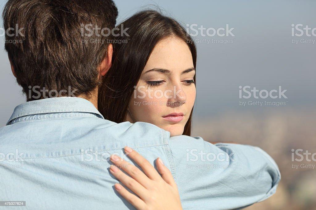 Sad woman hugging her boyfriend couple problems stock photo