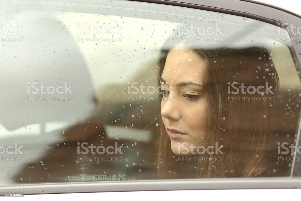 Sad woman looking down through a car window stock photo