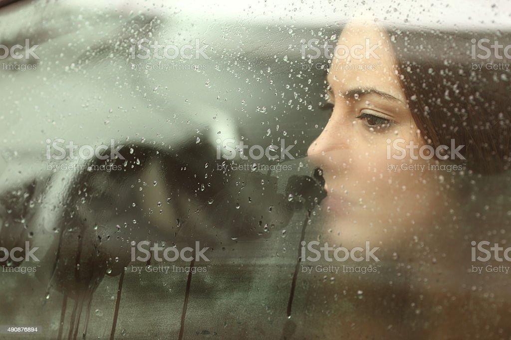Sad woman or teenager girl looking through a steamy car window