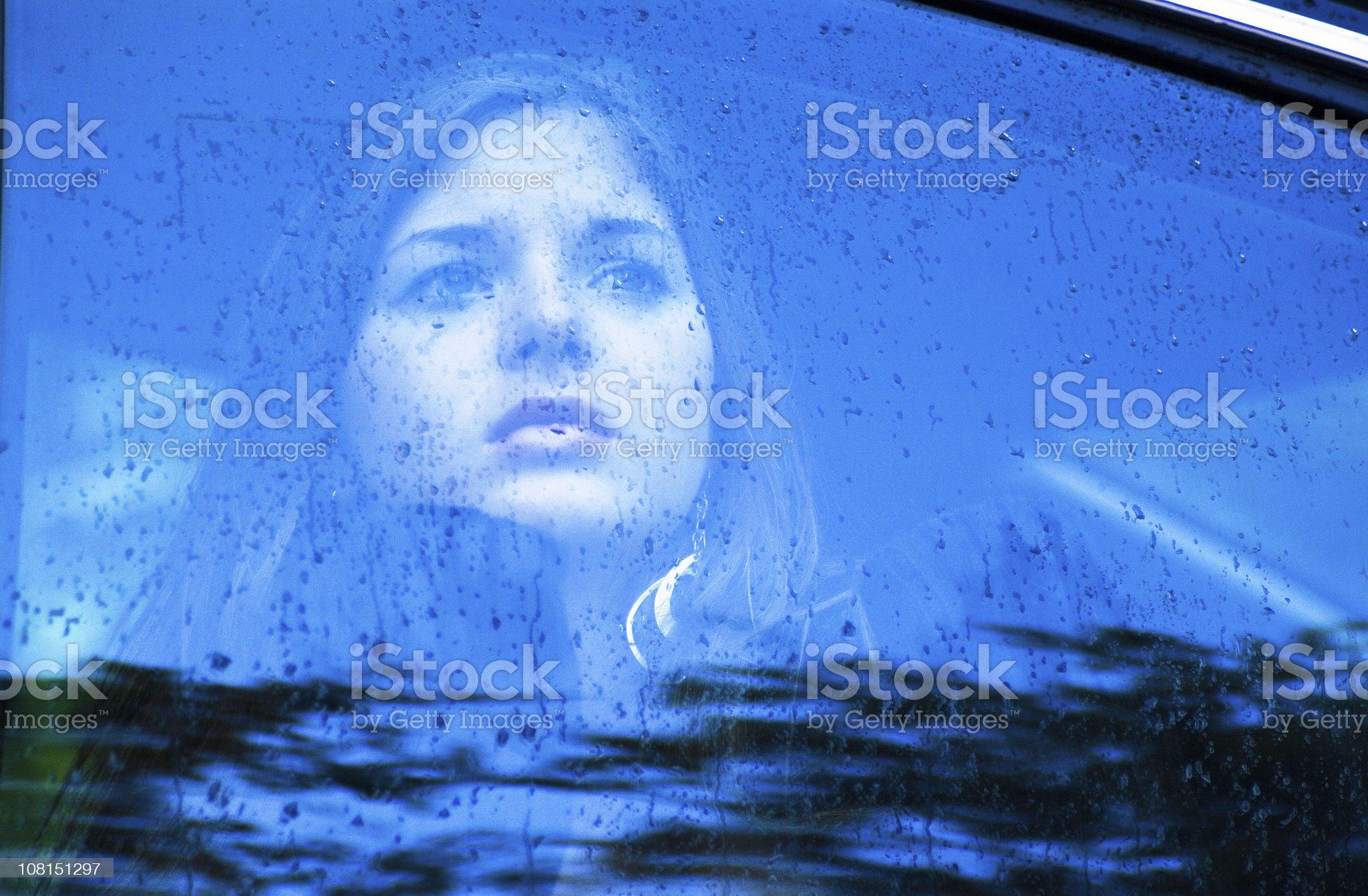 Sad Woman Looking Through a Window in the Rain royalty-free stock photo
