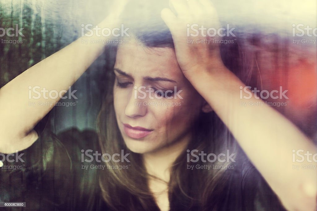 Sad woman looking through window on rainy day stock photo