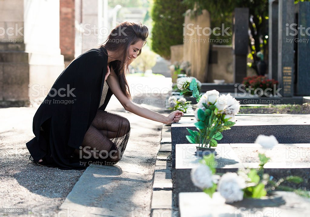 Sad woman on her knees in front of a grave stock photo