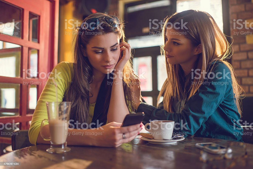 Sad woman reading text message to her friend in cafe. stock photo