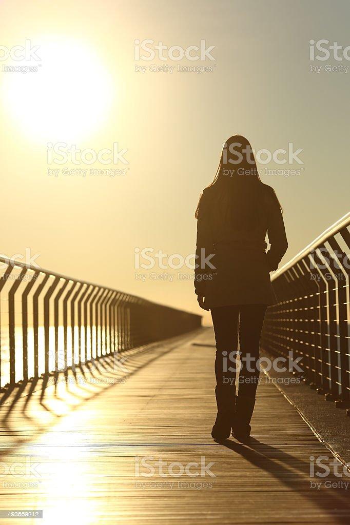 Sad woman silhouette walking alone at sunset stock photo