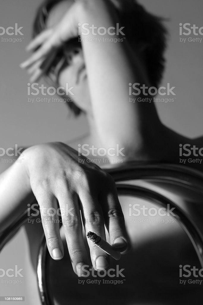 Sad Woman Sitting Backwards on Chair Smoking stock photo