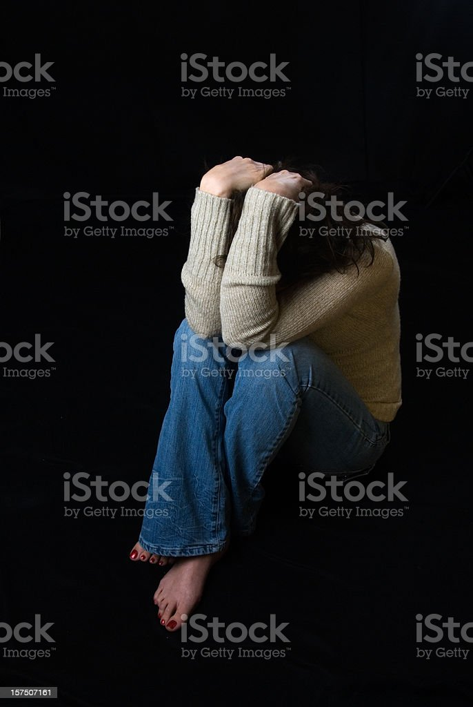 Sad woman sitting down covering her face stock photo