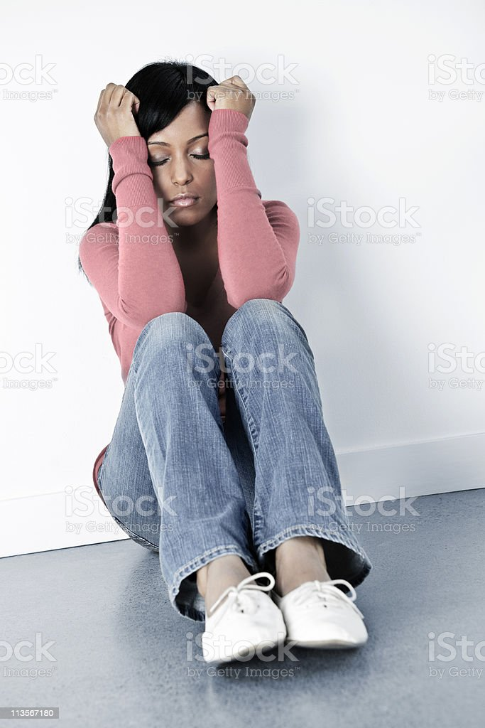 Sad woman sitting on floor with arms up and eyes closed royalty-free stock photo