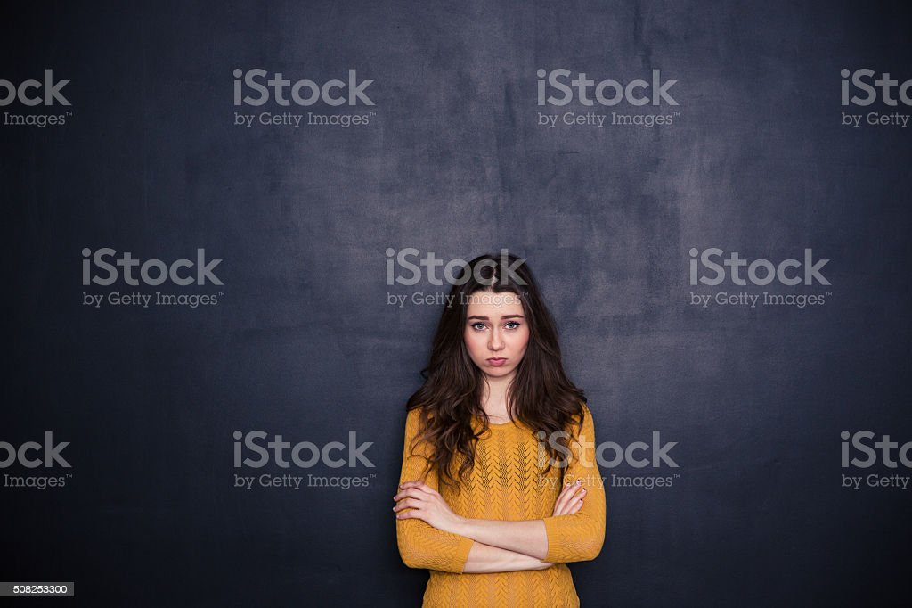 Sad woman standing with arms folded stock photo