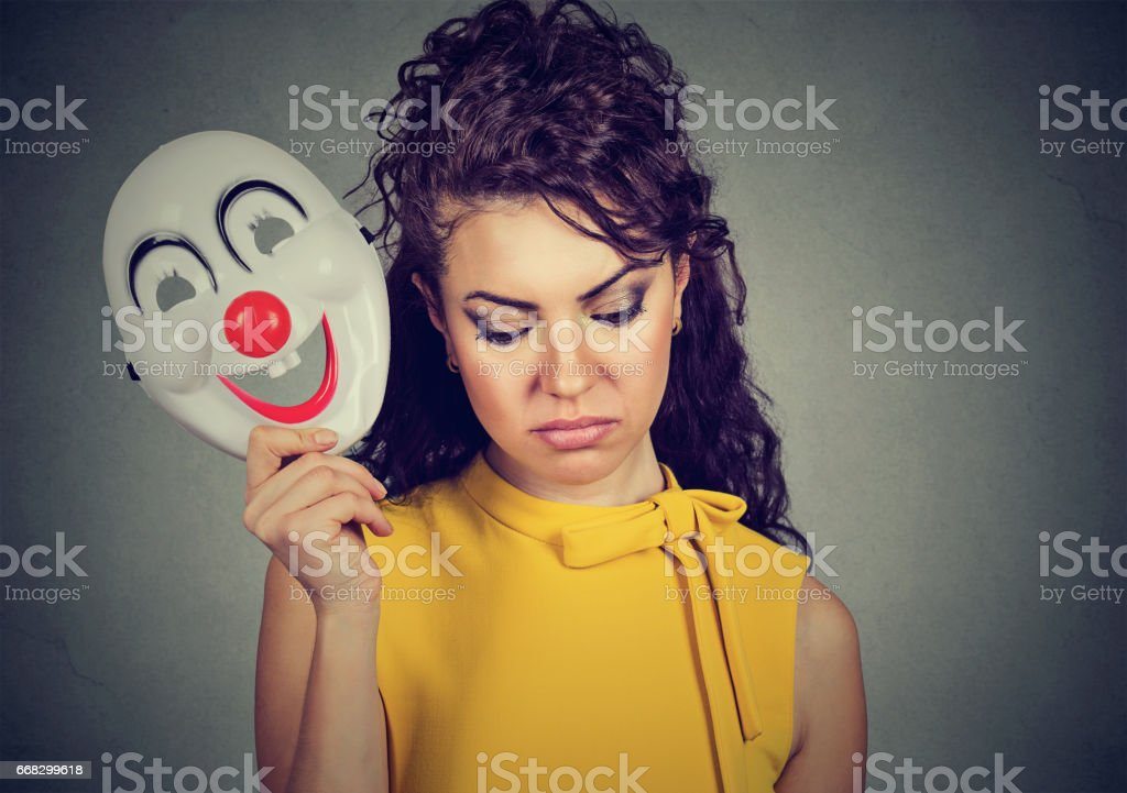 sad woman taking off clown mask expressing cheerfulness happiness stock photo