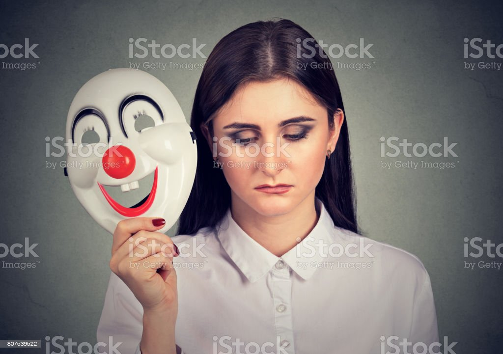 sad woman taking off clown mask expressing happiness stock photo