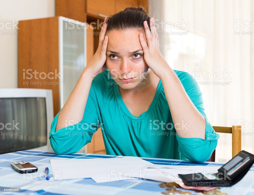 Sad woman with bills at the table stock photo