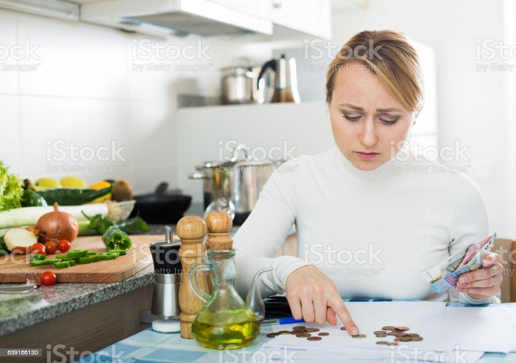 Sad woman with last money and bills stock photo