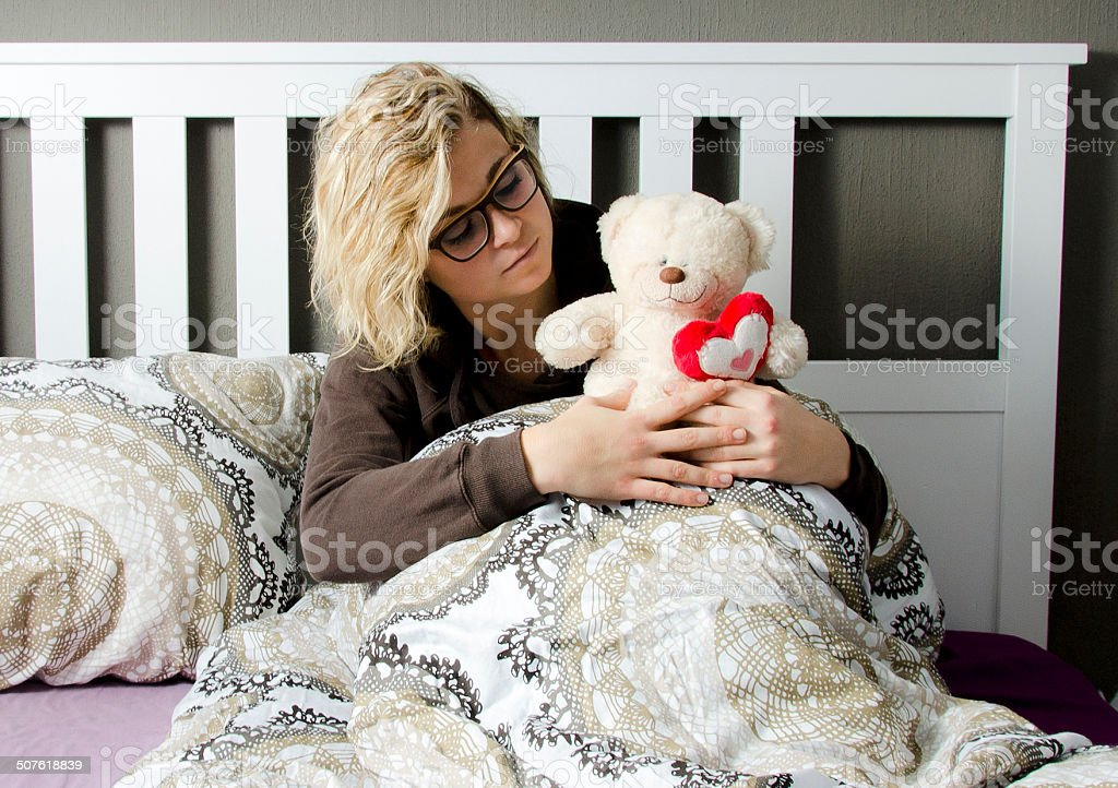 Sad woman with teddy bear in bed stock photo