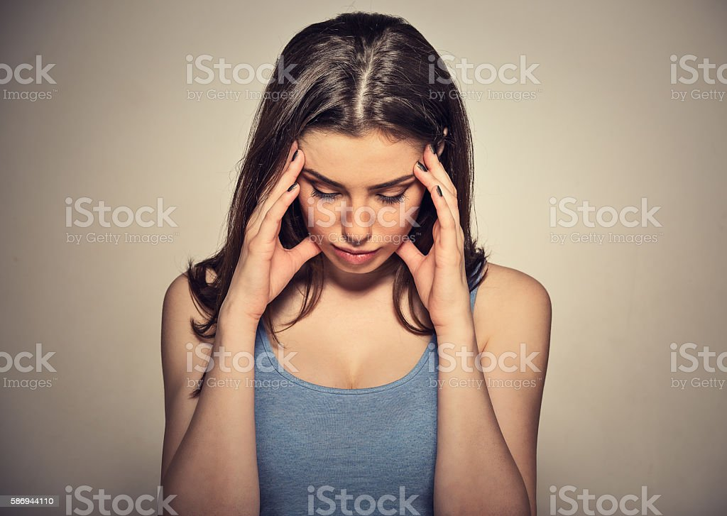 sad woman with worried stressed face expression looking down stock photo