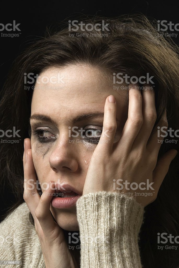 Sad woman's face with tears and smeared makeup royalty-free stock photo