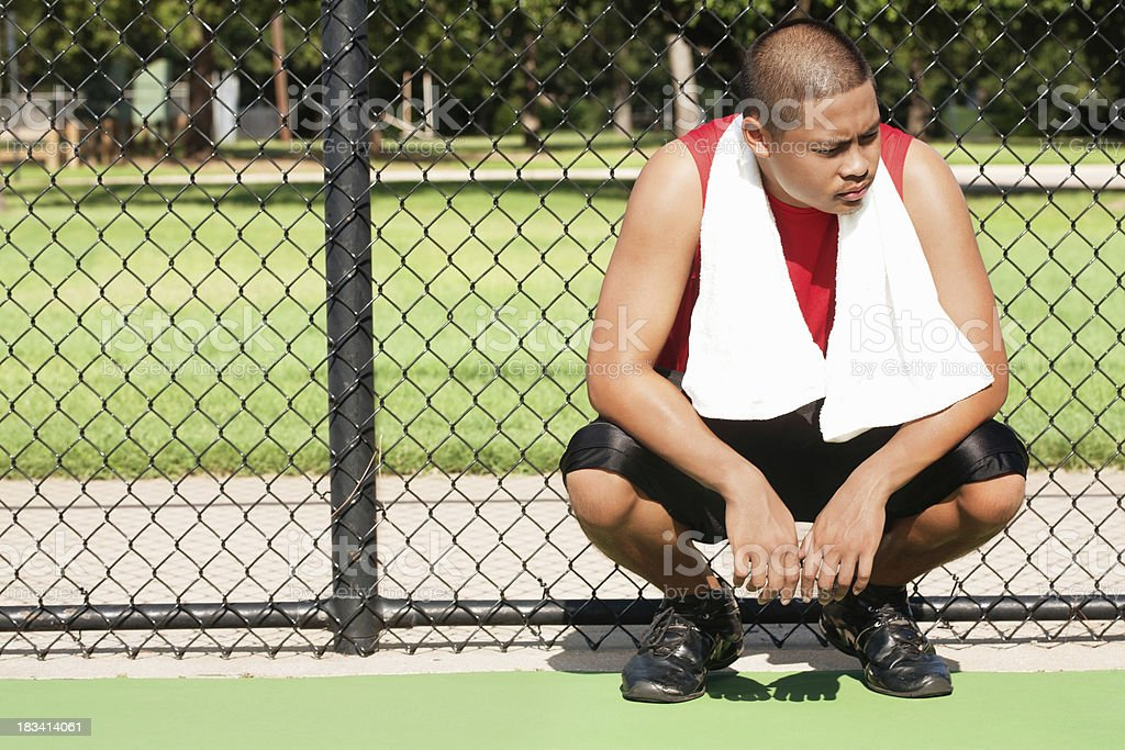 Sad Young Athlete Resting at a Court Fence royalty-free stock photo