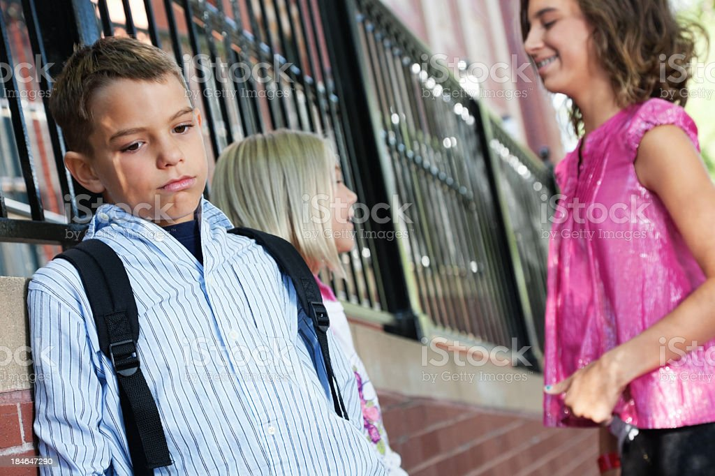 Sad young boy waiting outside school building royalty-free stock photo