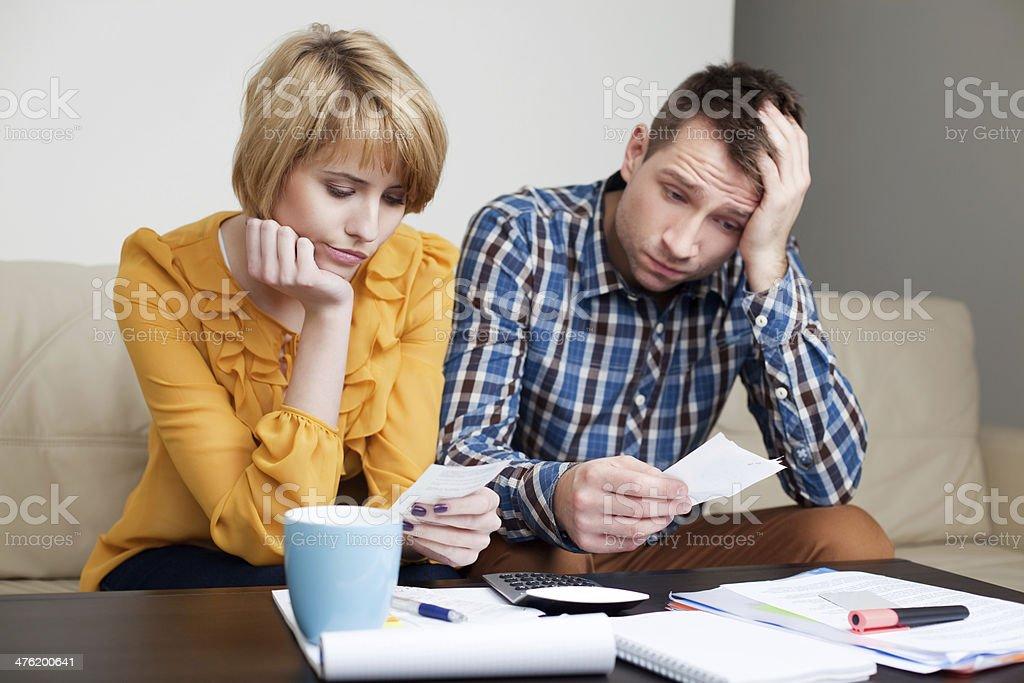 Sad young couple paying bills. stock photo