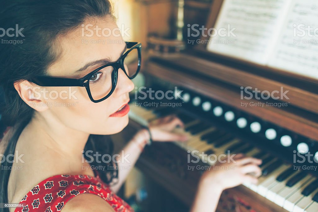 Sad young female pianist practicing at home stock photo