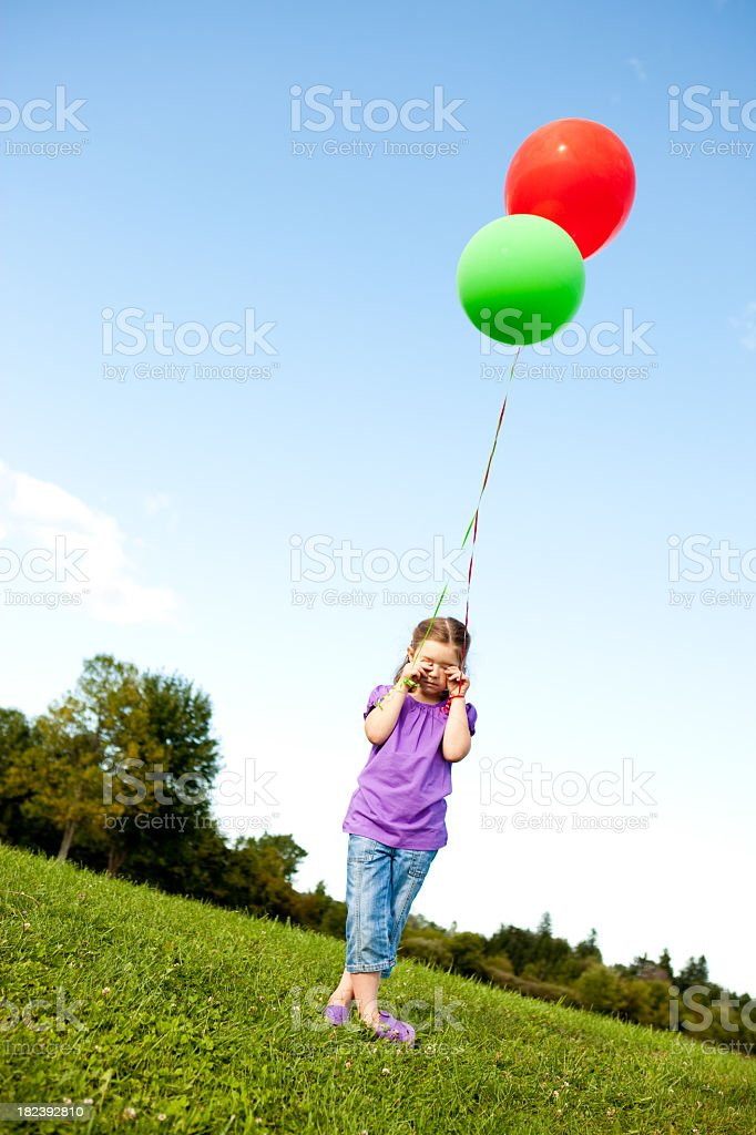 Sad Young Girl Holding Balloons Alone Outside royalty-free stock photo