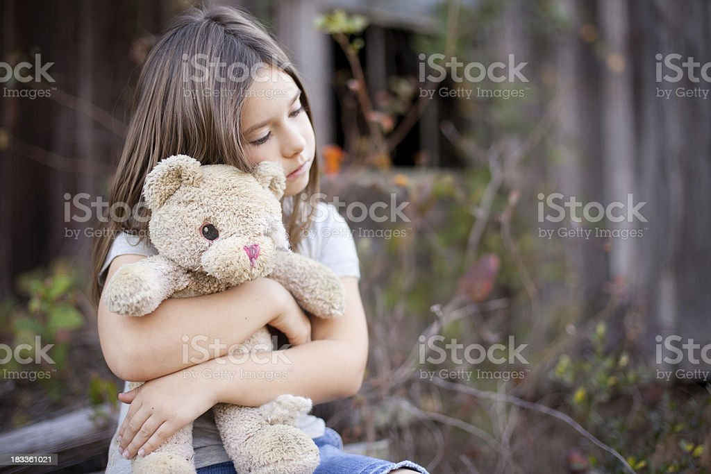 Sad Young Girl Hugging Old, Raggedy Teddy Bear stock photo