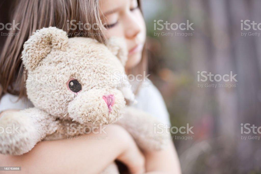 Sad Young Girl Hugging Old, Raggedy Teddy Bear stock photo