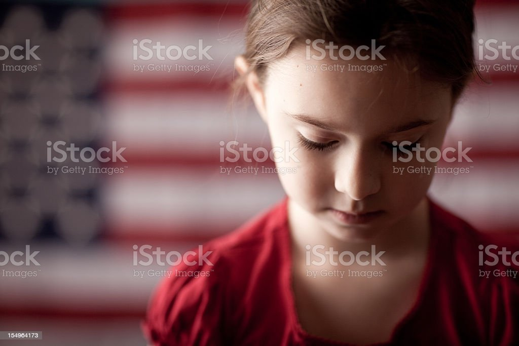 Sad Young Girl Looking Down in Front of American Flag stock photo