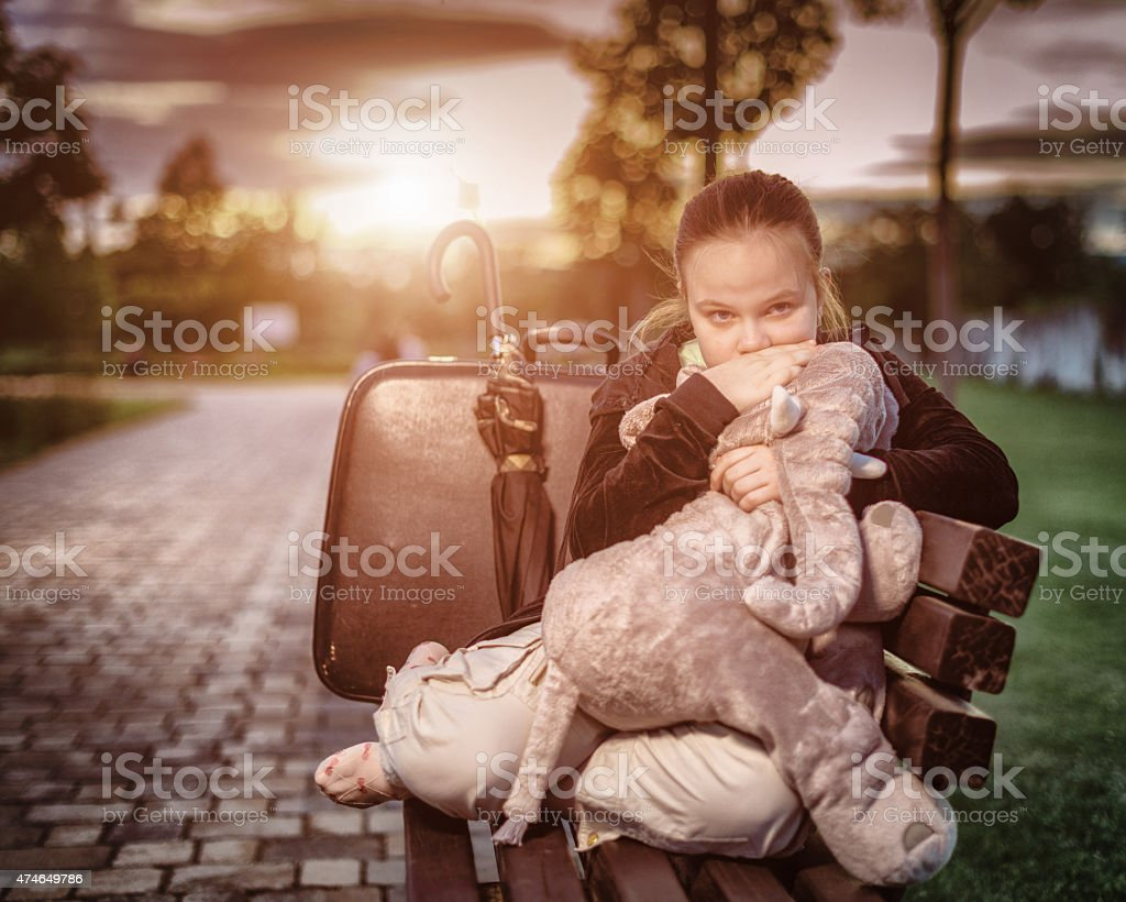 Sad young girl sitting on a bench stock photo
