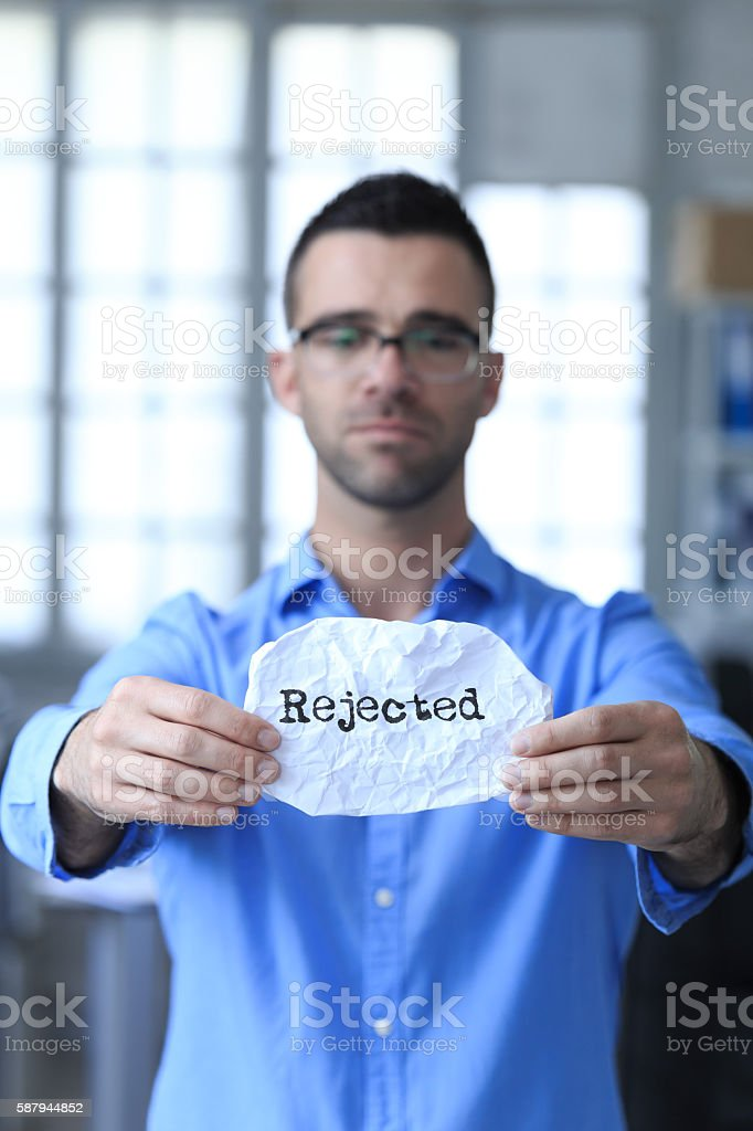 Sad young man holding a paper with sign 'rejected' stock photo