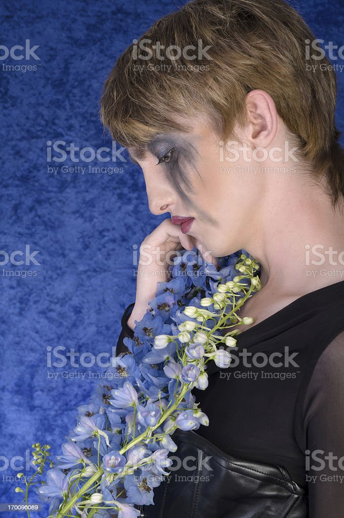 Sad young man holding flowers for comfort. stock photo