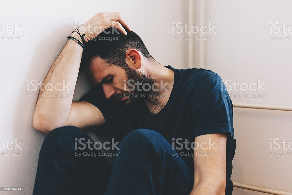 Sad young man sitting in the corner of the room stock photo