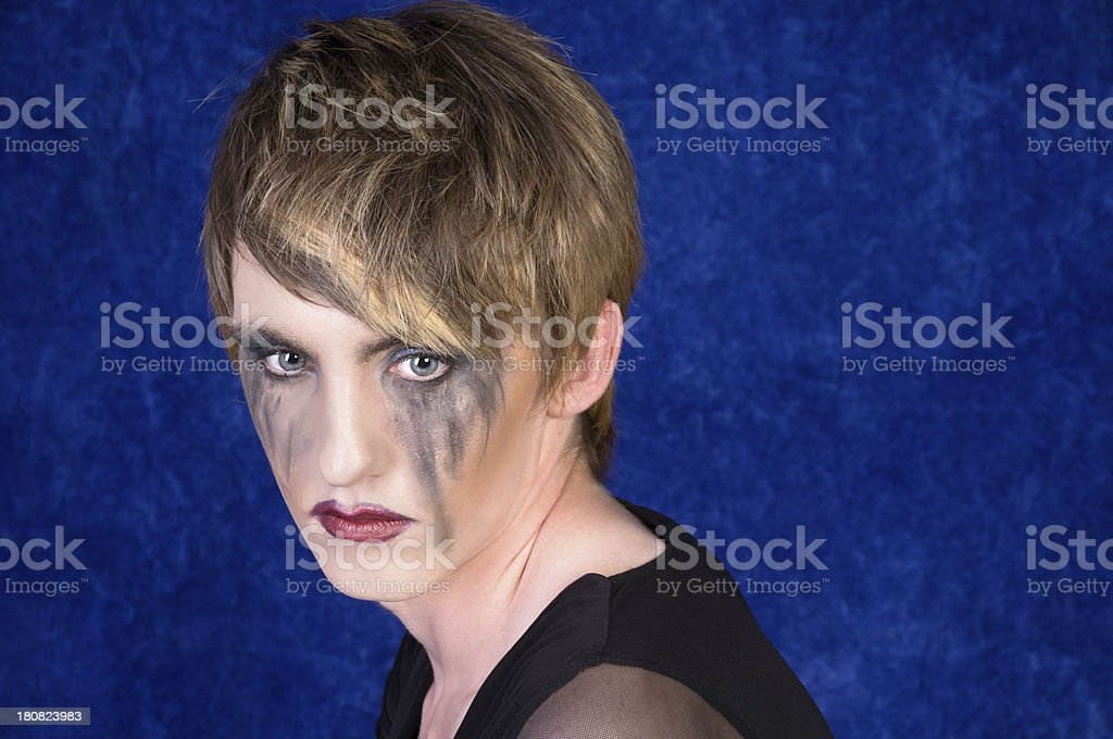 Sad young man with running eye makeup on blue. stock photo