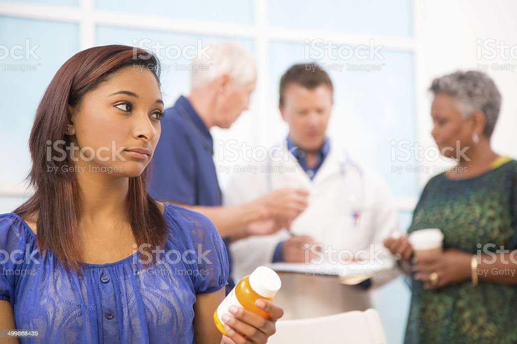 Sad young woman abuses prescription medications. Doctor, patients background. stock photo