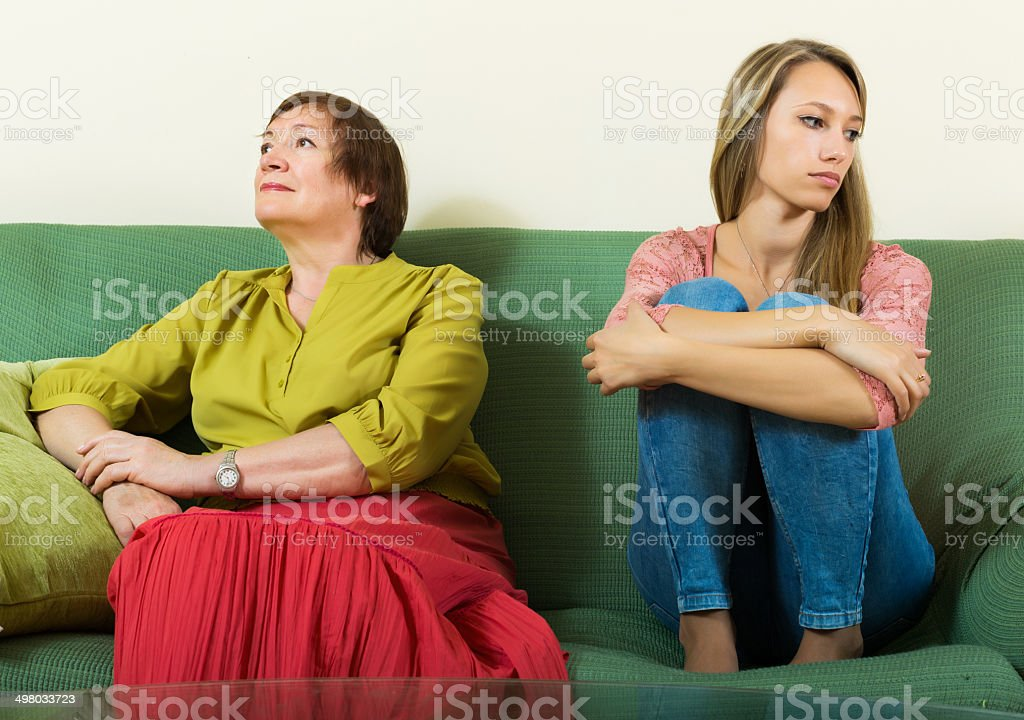 Sad young woman and  mature mother after conflict stock photo