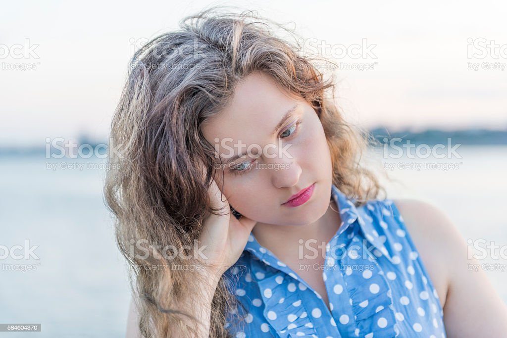 Sad young woman holding head and looking down stock photo