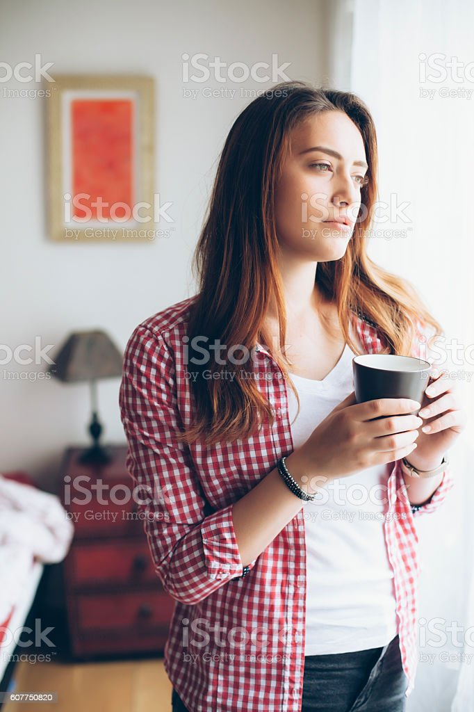 Sad young woman looking through window stock photo
