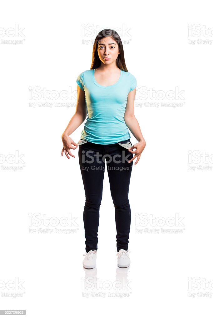 Sad young woman pulling out empty pockets from pants stock photo