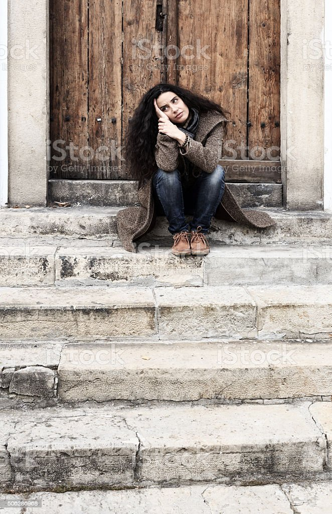 Sad young woman sitting on stairs at the door stock photo