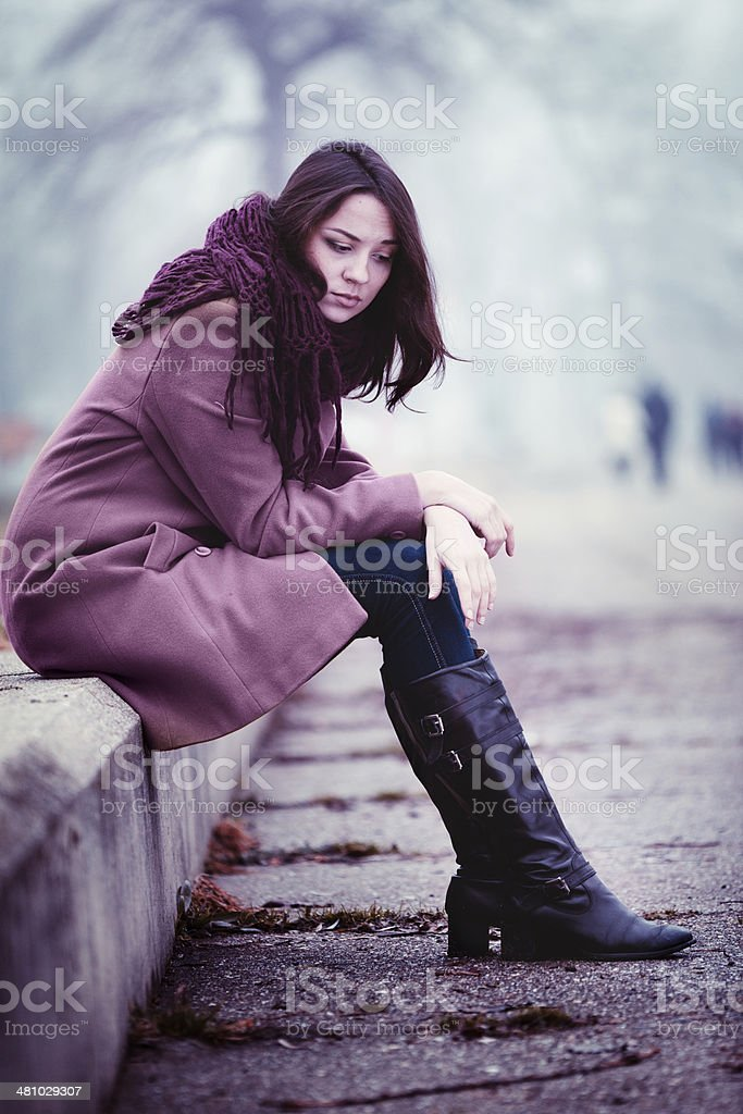Sad Young Woman Sitting Outdoors royalty-free stock photo