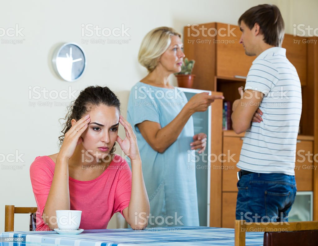 Sad young woman watching husband and mother having fight stock photo