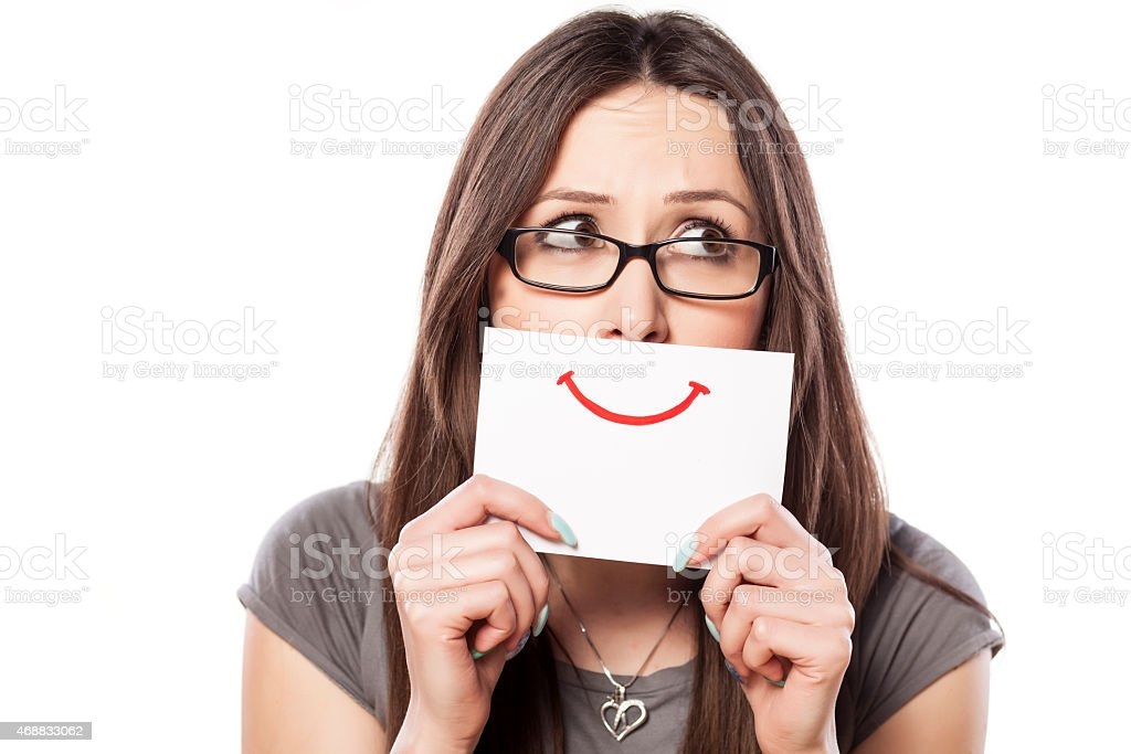 Sad young woman with smile painted on paper stock photo