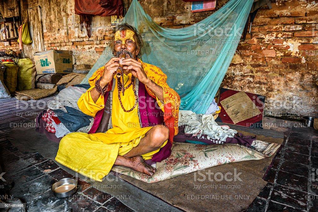 Sadhu baba plays a pipe in Pashupatinath Temple, Nepal stock photo