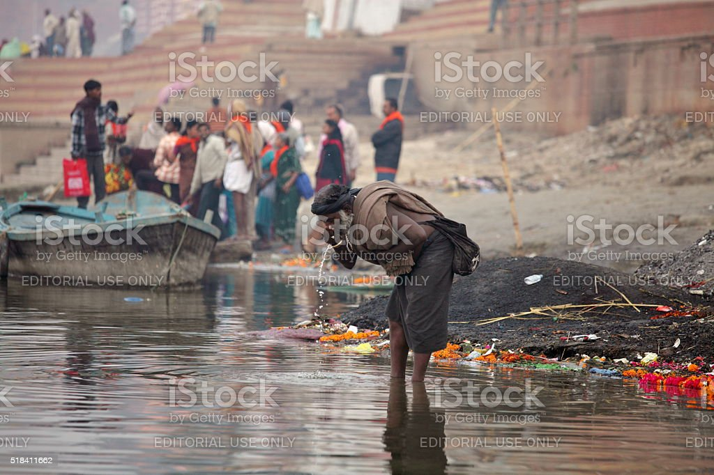 Sadhu from Aghori sect drinks water from Ganga river stock photo