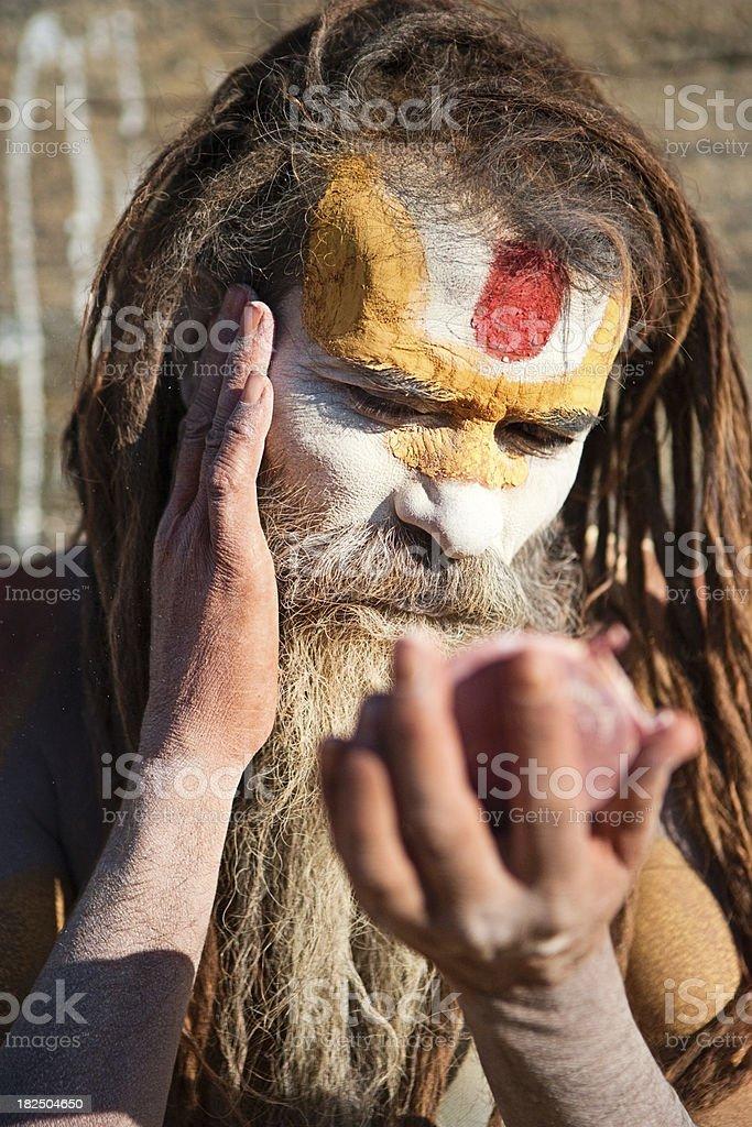Sadhu - holy man doing makeup stock photo