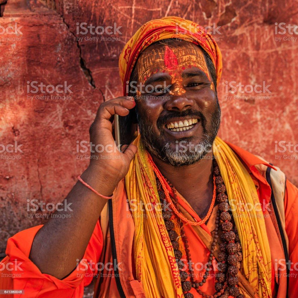 Sadhu - indian holyman using mobile phone stock photo