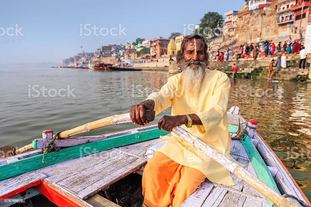 Sadhu rowing boat on the holy Ganges River in Varanasi stock photo