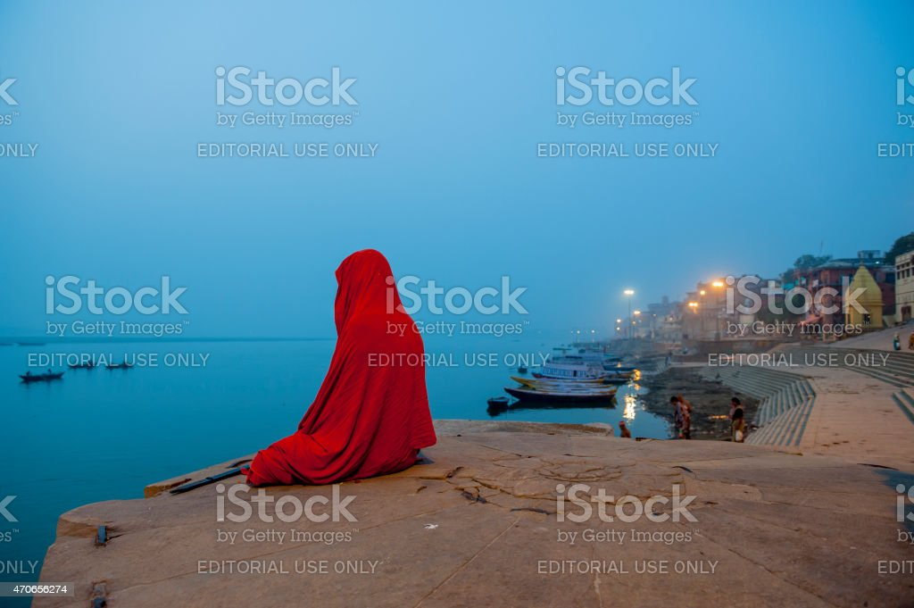 Sadhu sitting on the bank of Ganges River meditating stock photo
