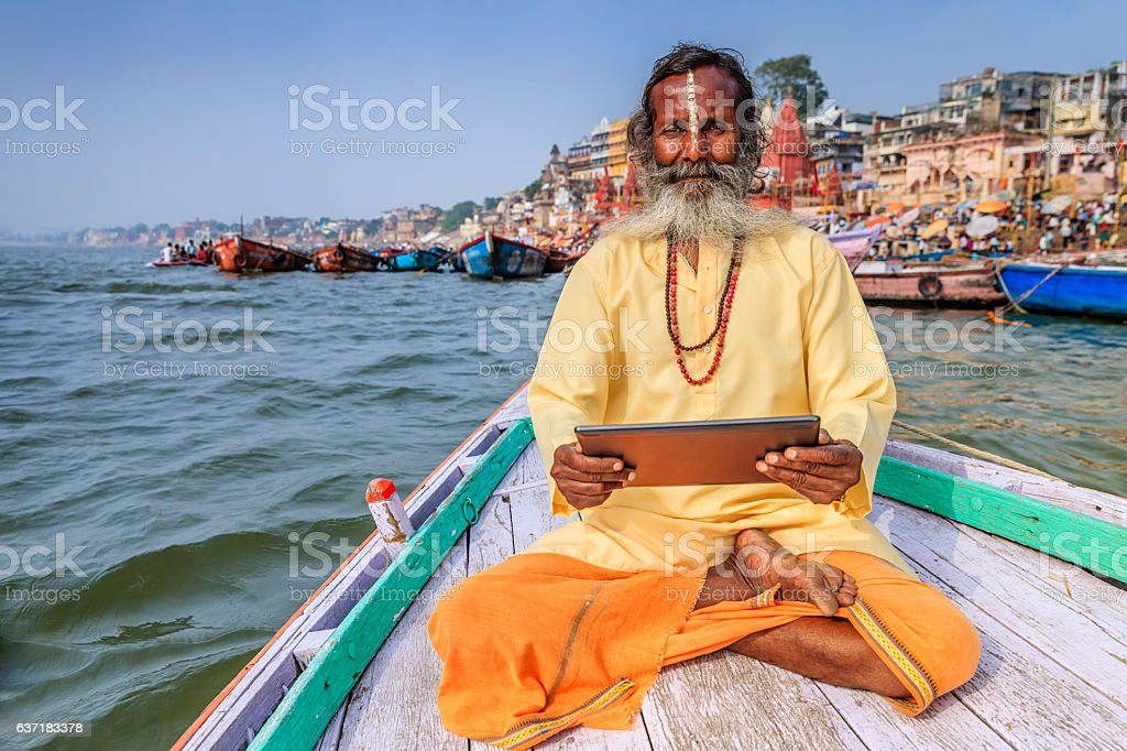 Sadhu using digital tablet in boat, Holy Ganges River, Varanasi stock photo