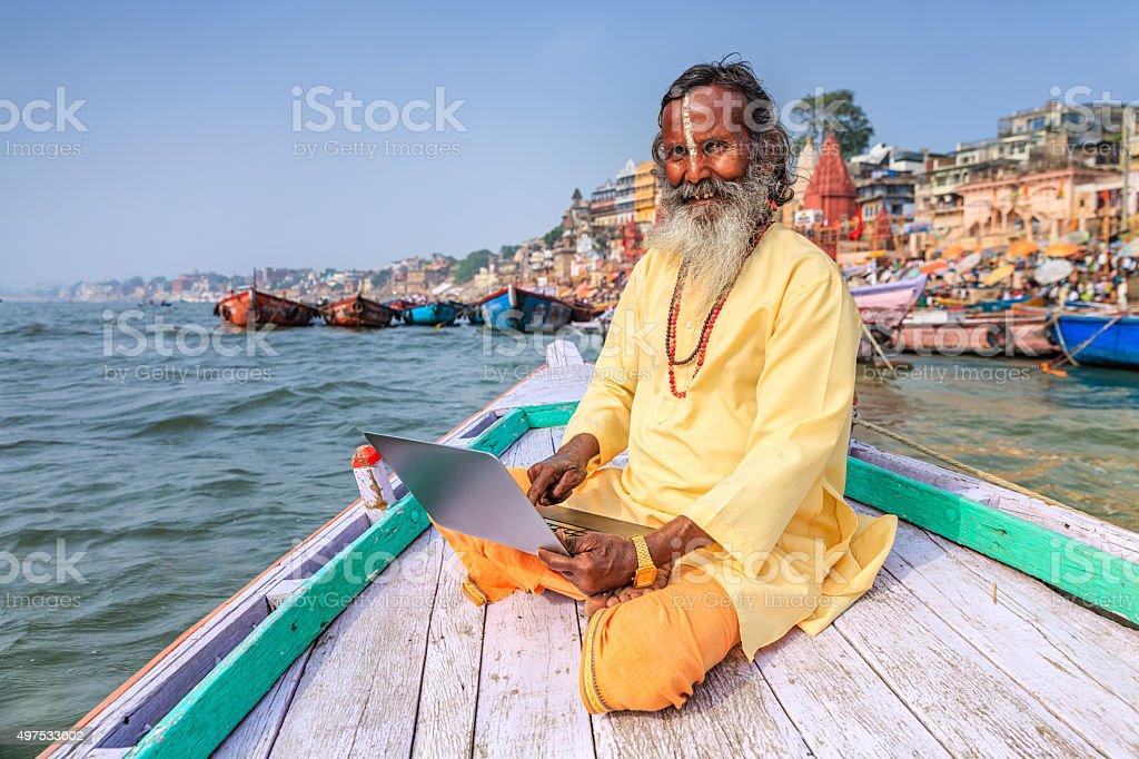 Sadhu using laptop in boat on Holy Ganges River, Varanasi stock photo